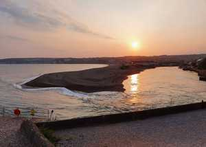 The beach at Seaton with the sunrise over the sandspit